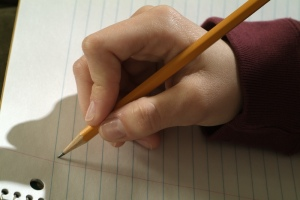 Hand grasping pencil about to write