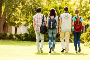 Rear view of teenage students walking together on university campus. Horizontal shot.