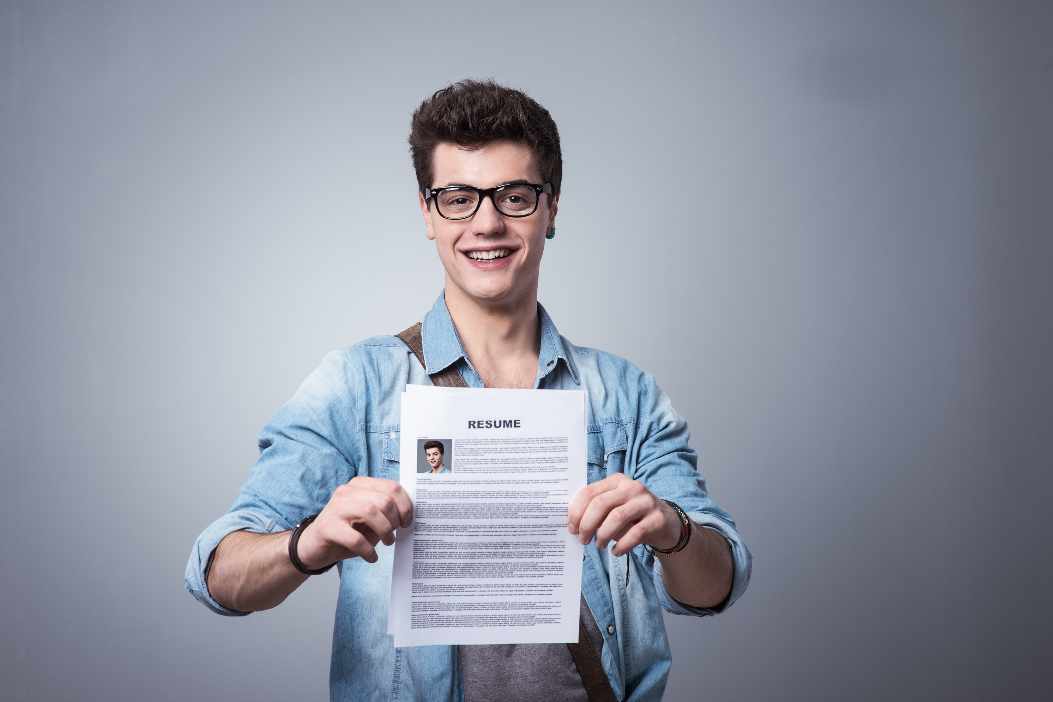 Young Smiling Man Holding His Resume Applying For A Job  Resume Edge